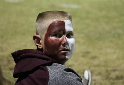 Student face painted with maroon and white